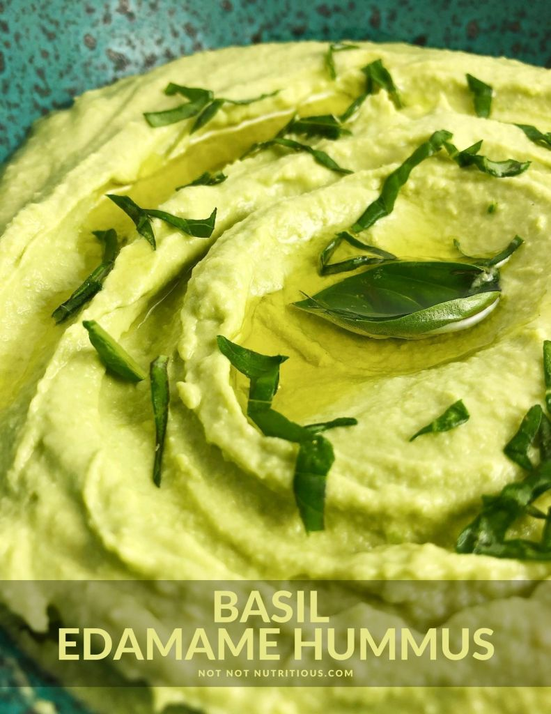 Close-up view of Basil Edamame Hummus in a blue-speckled bowl. Hummus is pale green thanks to the basil and edamame beans. Hummus is topped with a bit of olive oil and fresh basil leaves.