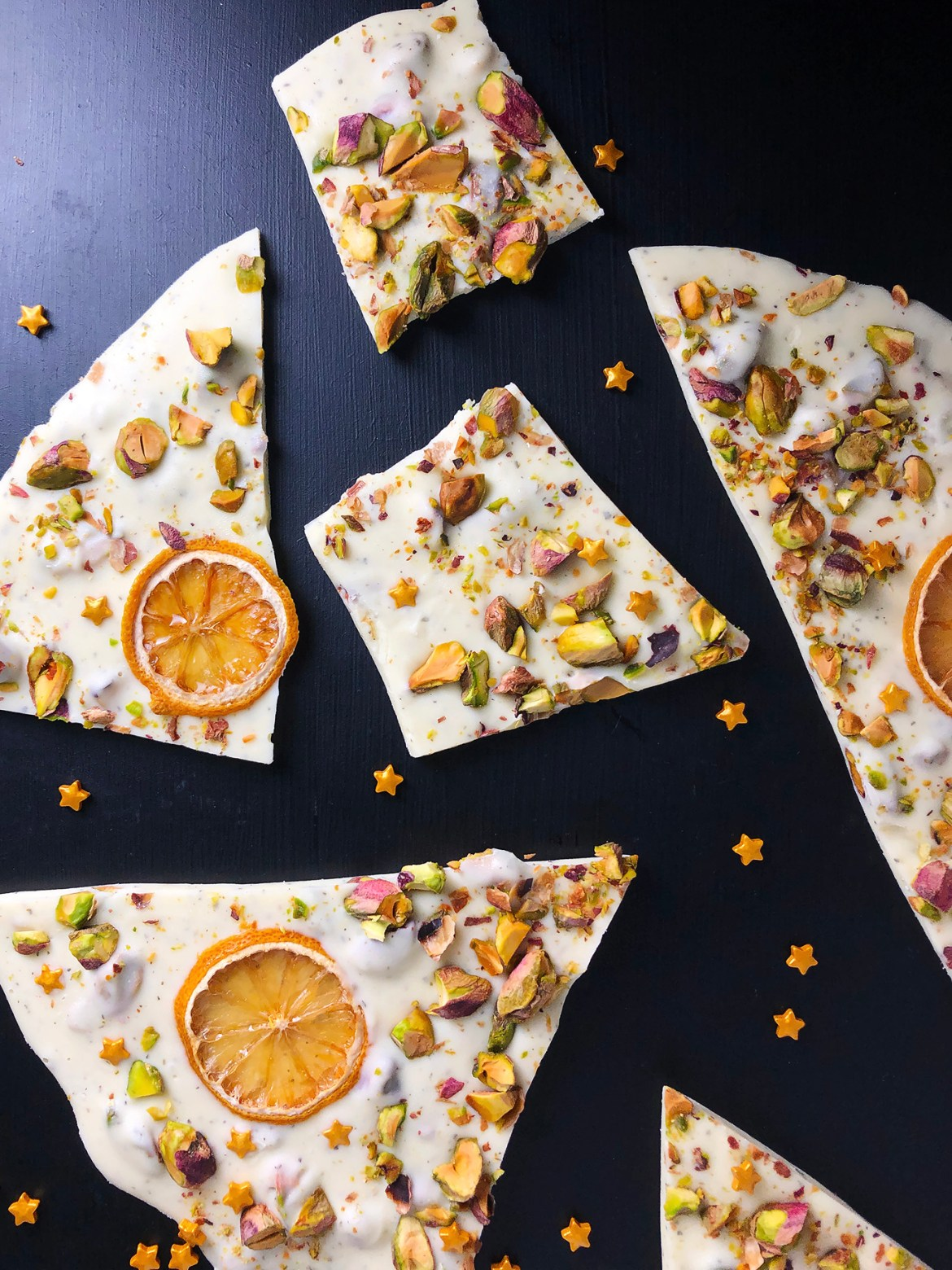 Top-down shot of white chocolate bark with lemon, green tea, pistachios, and oven-dried lemons, against a black background, sprinkled with gold candy stars.