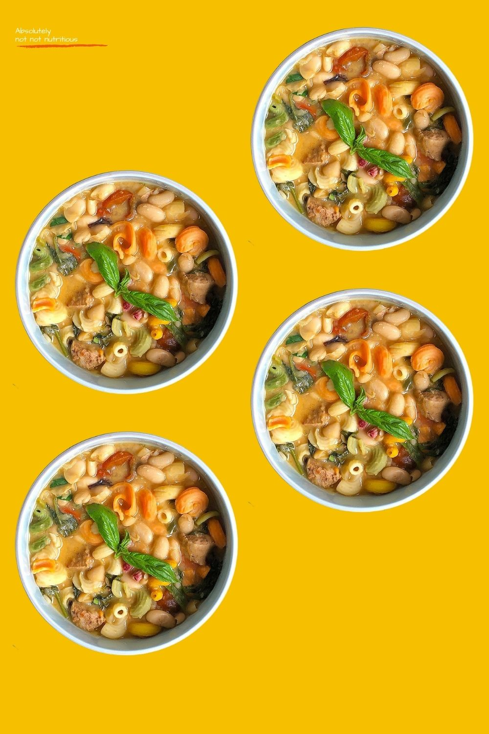Top-down view of 4 soup bowls against a gold background. Soup is made from white beans, garlic, cherry tomatoes, leafy greens, pasta, and vegetable broth. Soup is garnished with a sprig of basil. Text on top-left corner of image reads Absolutely not not nutritious