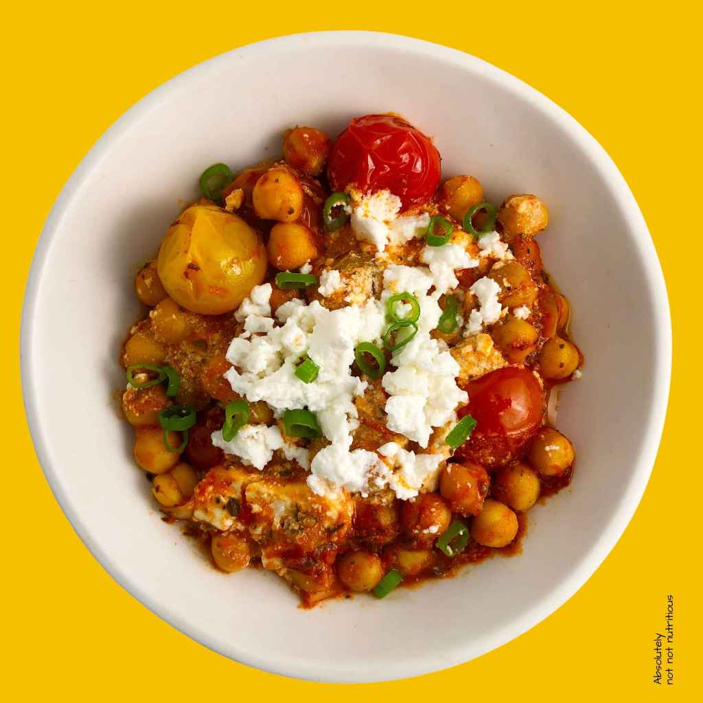 Top-down, close up image of white bowl of Chickpea Feta Bake, made with cherry tomatoes, chickpeas, feta, ginger, and dried mint. Topped with feta cheese and green onions.