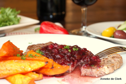 Steak with pomegranate-berry sauce  and yellow sweet  potato wedges