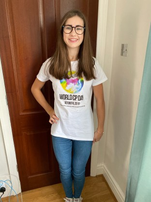 I have a World CP Day top its white the globe is made up of yellow, pink and blue with blue jeans. I have straight hair glasses on and am stood against a dark brown wood door.