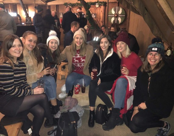 Myself with 6 other friends in a Christmassy environment sat with drinks on some benches.