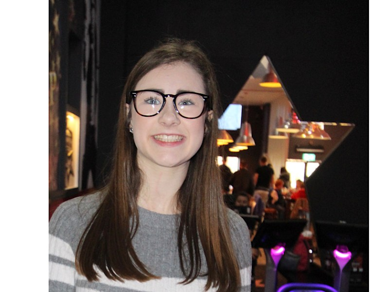 A photo of myself with straight, hair, glasses, minimal makeup in a grey dress with 2 white stripes across my lower chest. The background is dark and then there an a star outline and you can see people in the back but this is out of focus.