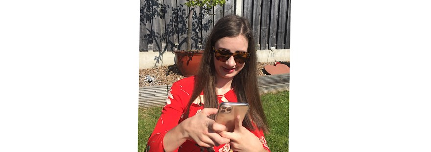 Myself with my sunglasses on with straight hair in a red dress with flowers on, looking at my phone. The sun is shining I am sat on my garden, on the grass then fence is in view with a small tree.