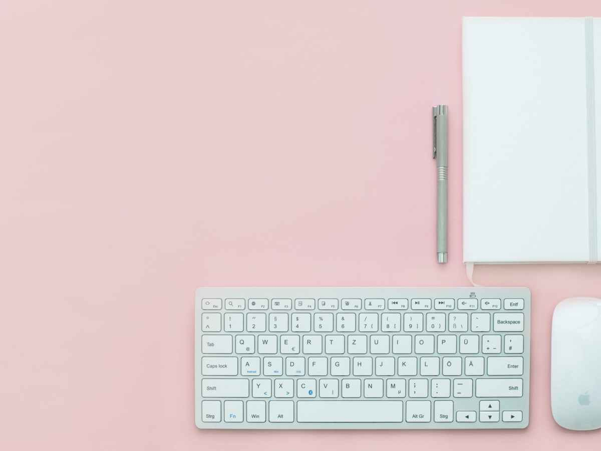 A brides eye view of a pink background with an apple mouse and keyboard, a grey pen and white notebook which has a material band round it to keep every together.