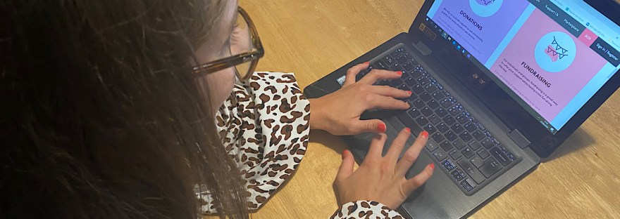 Myself wearing a leopard print blouse, looking at Skiggle's website, on my laptop, this is from a side angle so you can just see a bit of my hair and the frame of my glasses. The screens shows purple and pink boxes telling you about Skiggle's SOS.