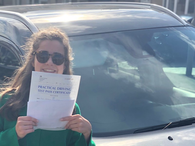 Myself in front of my grey car (Ford Tourneo Connect) wearing a green knitted jumper holding up a practical driving test certificate.