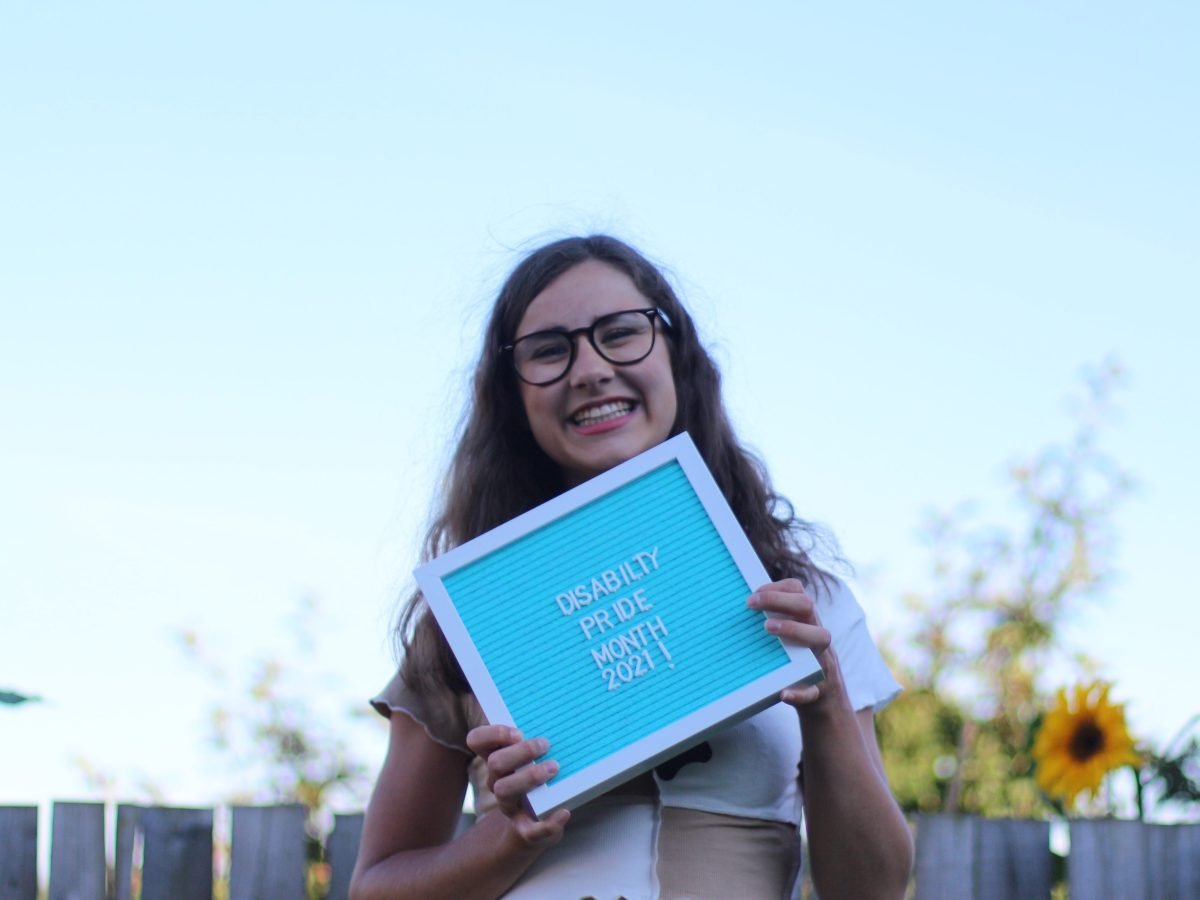 Myself outside with curly hair and my glasses on holding up a light blue letter board saying 'Disability Pride Month 2021.