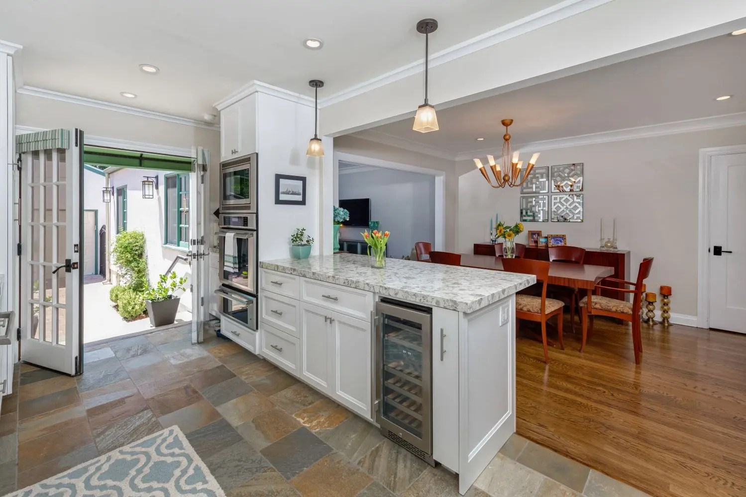 Kitchen peninsula with ovens and wine cooler.