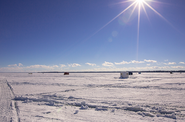 snow covered lake simcoe with ice fishing huts in the distance