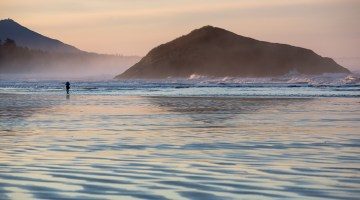 woman strolls on an endless stretch of beach in tofino at sunrise