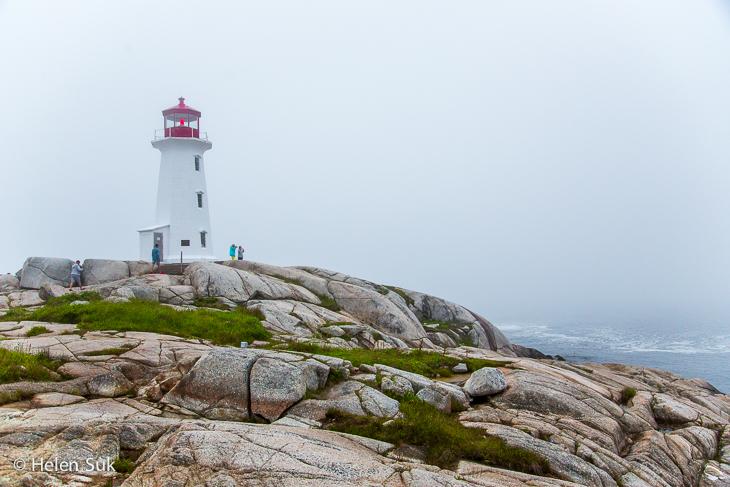 lighthouse under fog at peggys cove