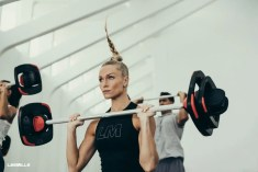 Woman lifting barbell in Les Mills Grit class