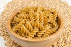 bowl of spelt pasta spirals on a bed of spelt