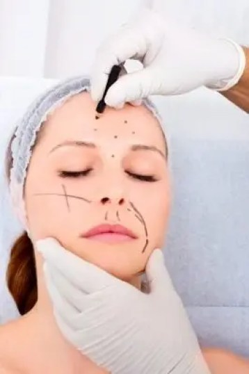 Surgeon drawing on a woman's face