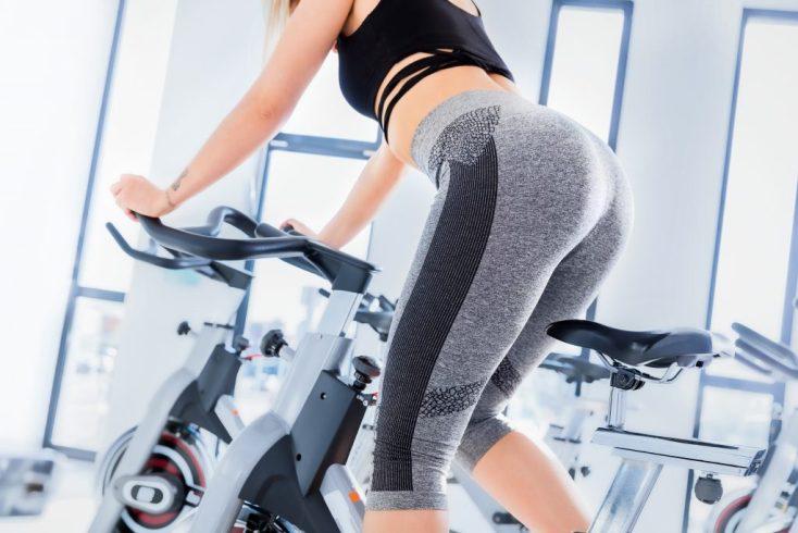 Woman in grey leggings on spinning bike