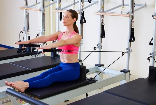 woman wearing a pink top and purple leggings using a Pilates reformer