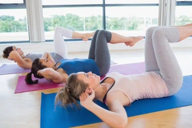 three women lying on the floor on a Pilates Mat Class