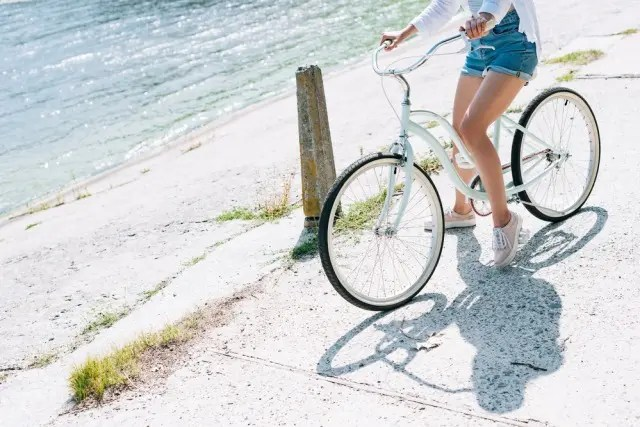 Woman sitting on a bike by water