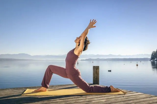 woman in yoga pose by the sea