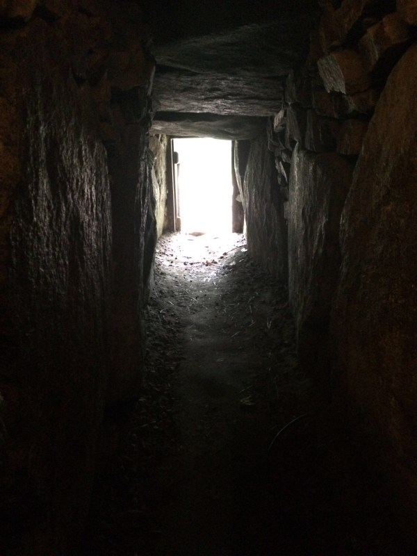 A view of a dark passageway inside a tumulu, looking toward the bright entrance undergroud