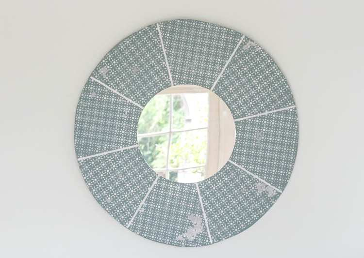 Stencil a diy wall mirror easily with a piece of wood, some paint, a small round mirror and an easy stencil. Perfect addition to your home decor wall art.