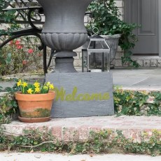Ideas for decorating a spring front porch, featuring moss and other greenery and a Cricut-made 'moss painted' Welcome sign.