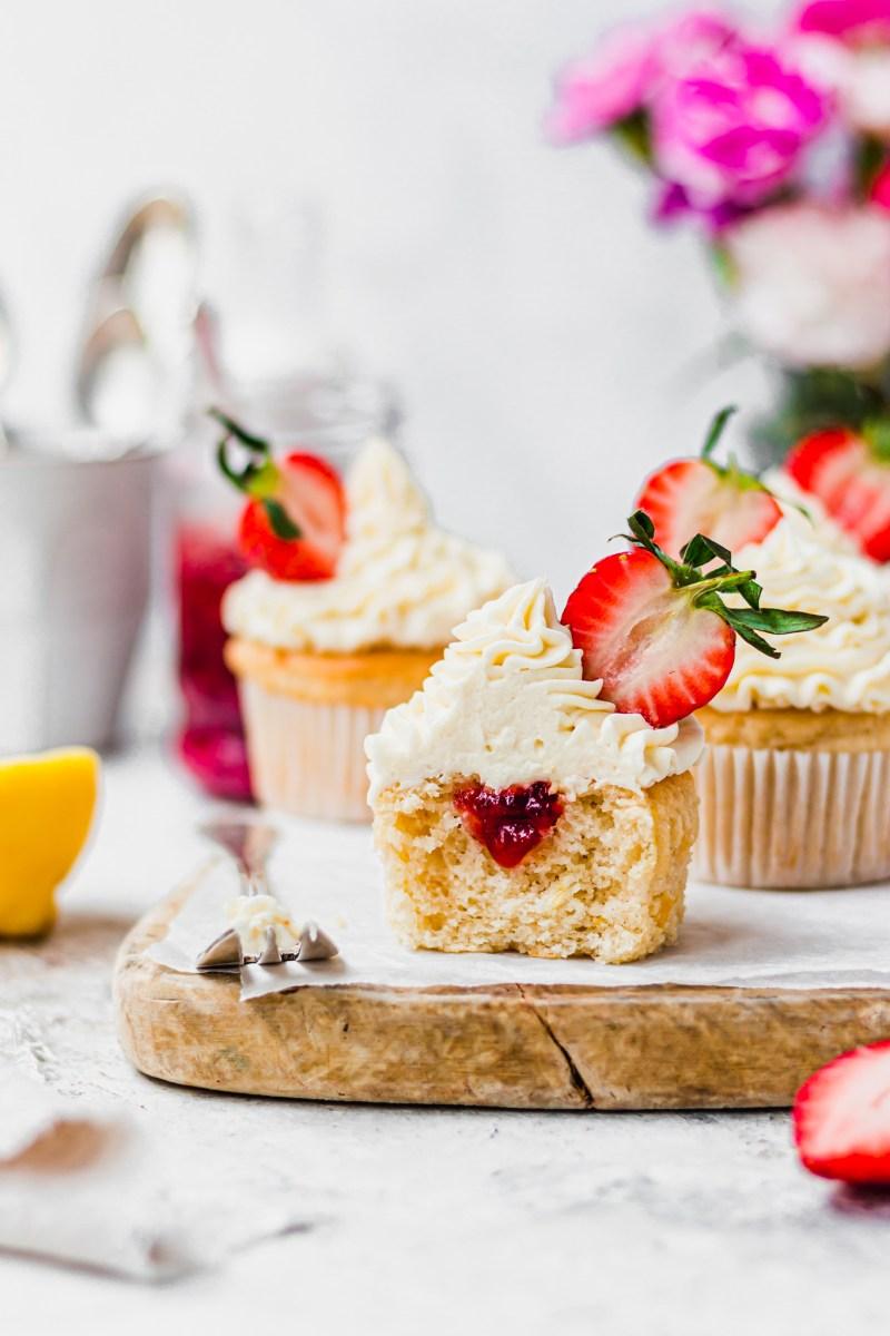 A Vegan Lemon Strawberry Cupcakes cut open with a jam centre