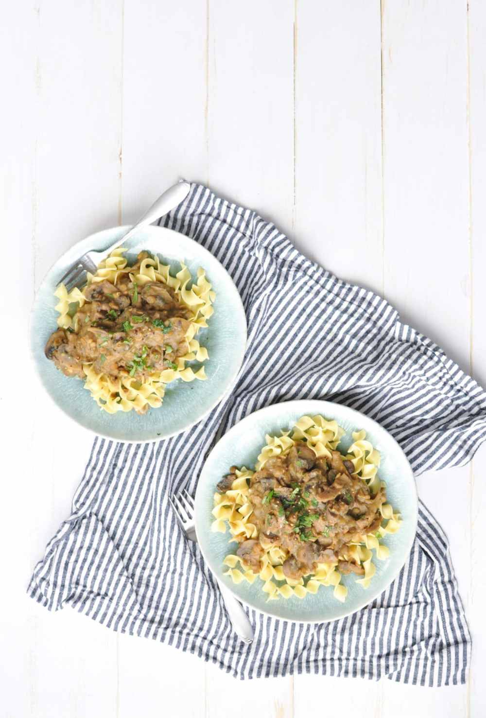 Two plates with lentil stroganoff over pasta