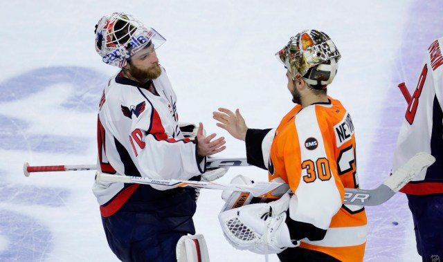 Washington Capitals' Braden Holtby, left, and Philadelphia Flyers' Michal Neuvirth meet after Game 6 in the first round of the NHL Stanley Cup hockey playoffs, Sunday, April 24, 2016, in Philadelphia. Washington won the game, 1-0, to clinch the series 4-2. (AP Photo/Matt Slocum)