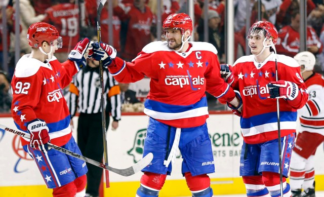 Mar 15, 2016; Washington, DC, USA; Washington Capitals left wing Alex Ovechkin (8) celebrates with Capitals center Evgeny Kuznetsov (92) and Capitals defenseman Dmitry Orlov (9) after scoring the game-winning goal in overtime against the Carolina Hurricanes at Verizon Center. The Capitals won 2-1. Mandatory Credit: Geoff Burke-USA TODAY Sports