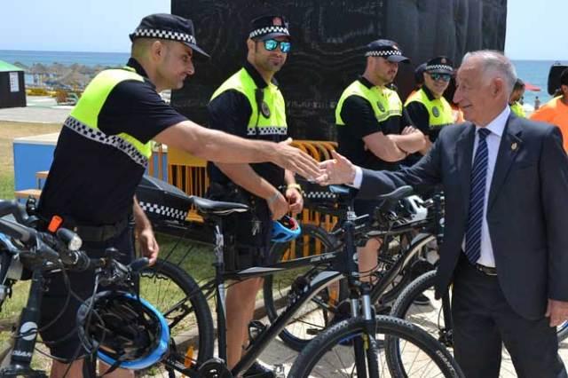 Amat saluda a los agentes que recorrerán el paseo marítimo en bicicleta.
