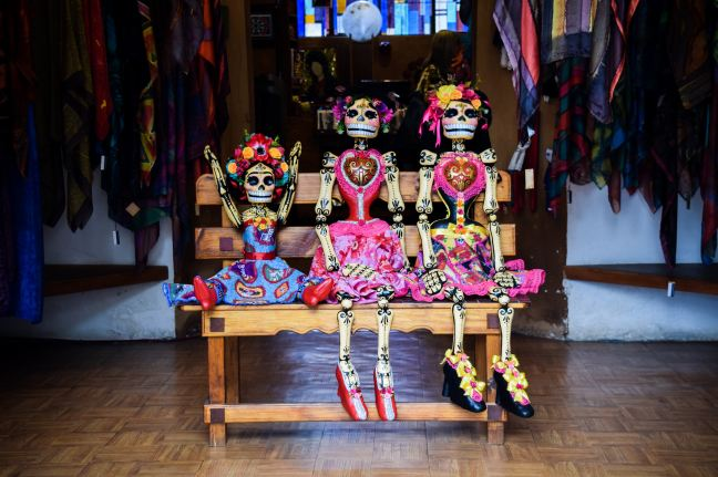 three Frida Kahlo skeleton dolls sitting on bench Photo by Valeria Almaraz on Unsplash