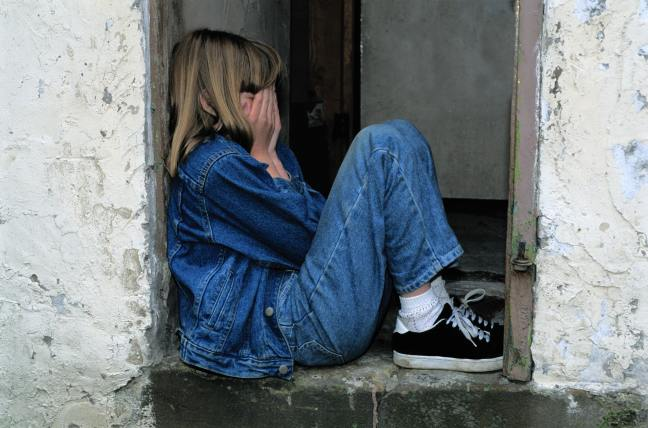 Girl crying in doorway. Photo by Pixabay.