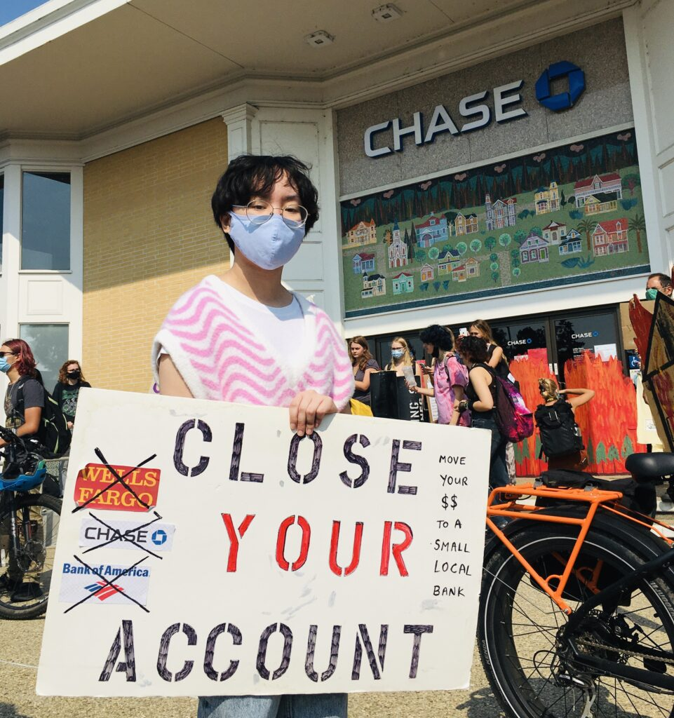 Youth for Climate Justice action 9-24: UCSC student with Close Your Account sign in front of Chase - photo by Ami Chen Mills Naim