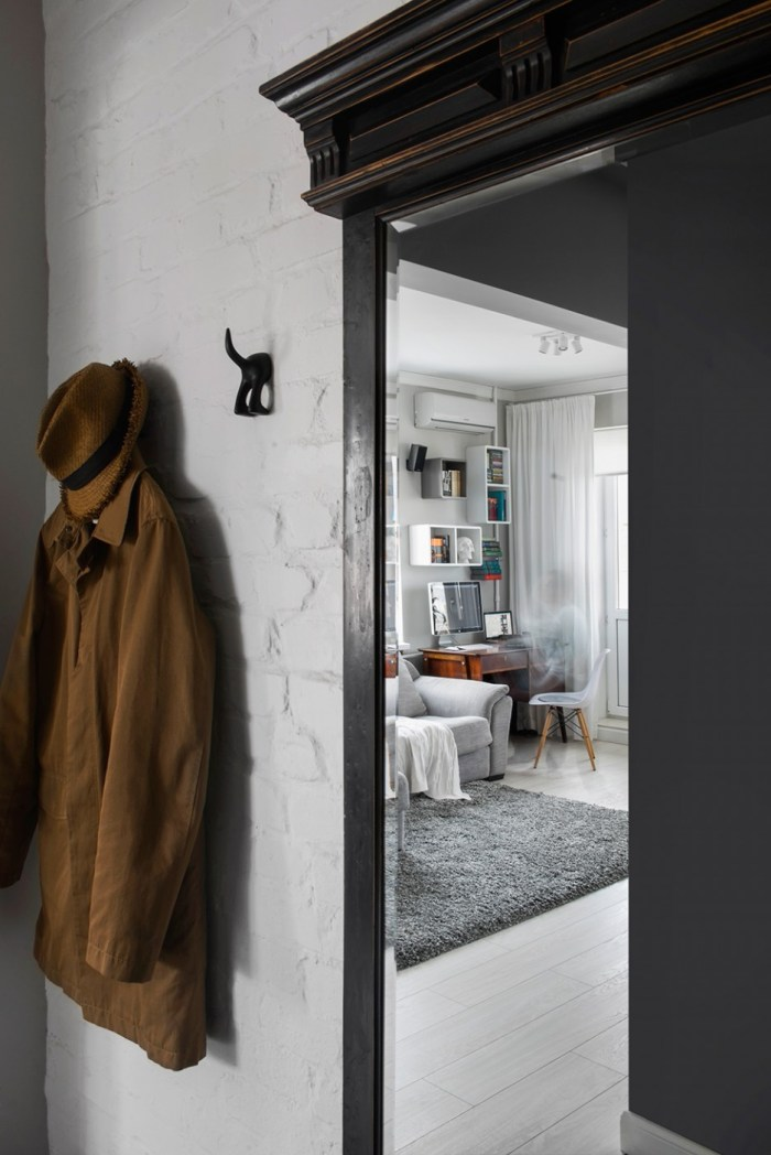 Artistic-Wall-Details-in-Moscow-Apartment-Entryway-Area-Decorated-with-Unique-Coat-Hooks-Beside-thw-Brown-Coat-and-Hat-936x1402