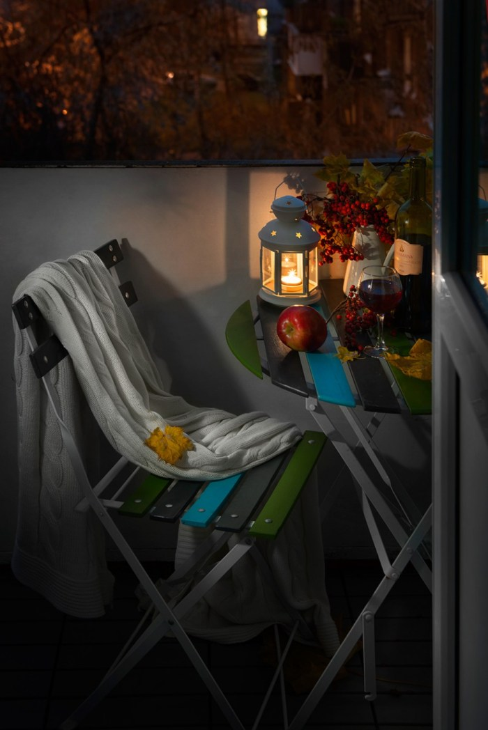 Romantic-Terrace-Area-View-by-Night-with-Classic-Lantern-as-Illumination-Applied-Also-Colorful-Chair-and-Table-with-Wine-and-Vase-936x1402