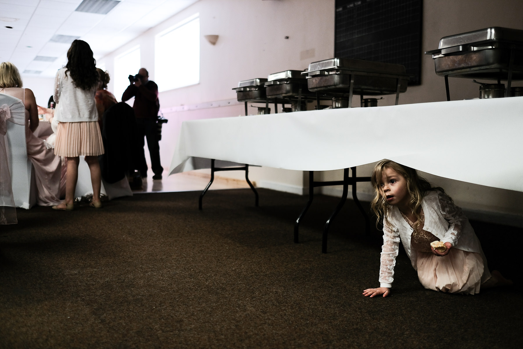 girl under table at wedding