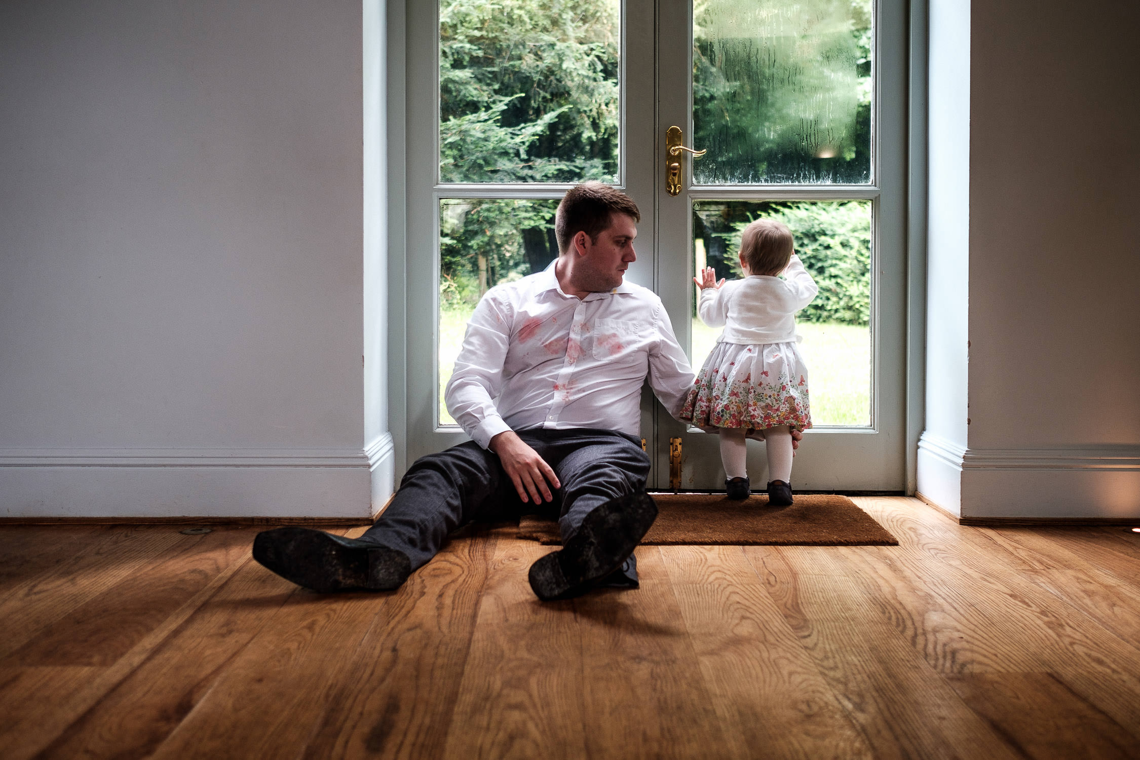 man with messy shirt sitting on floor with girl
