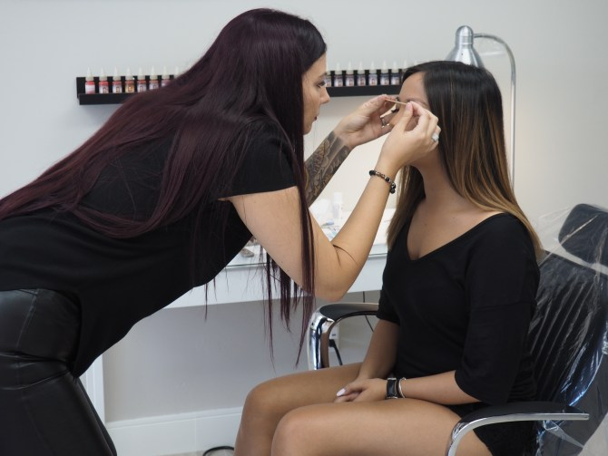 Amber checking Chelsea's eyebrows for balance.