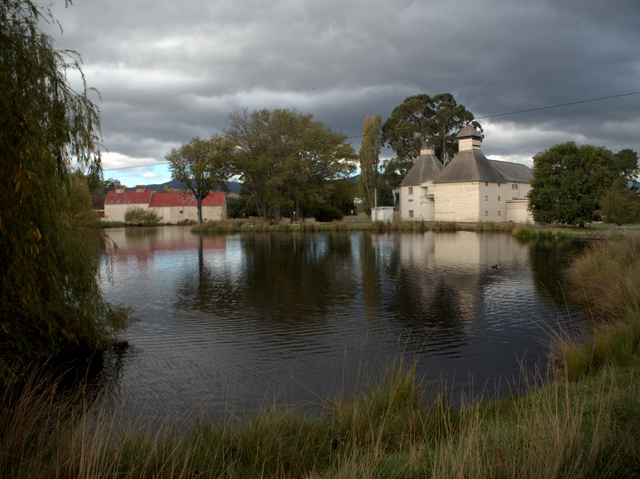A series of historic oast houses surround a pond at Bushy Park. The Text Kiln is on the right.