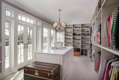 beautiful white walk in closet with french doors and large island