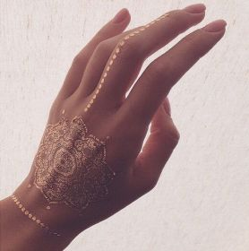 Picture Of gorgeous mandala gold henna tattoo on the hand