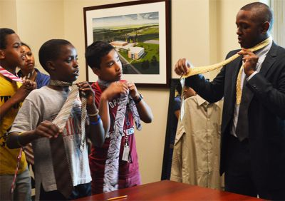 Local hip-hop artist George Moss teaches students how to tie a tie