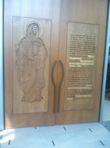 Carved wooden doors depicting the life of Mary Magdalen lead into the worship space.
