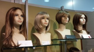 Professionals help fit and style wigs for clients.