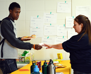 Special education paraprofessional Erin Kosten accepts Godwin Bucks from a student.