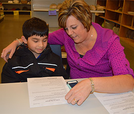 Third-grade student Daniel Rangel-Zavala works with tutor Joy Howard, who also is a paraprofessional for Kelloggsville Public Schools.