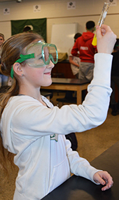 Amaris Russell examines a chemical reaction caused by mixing potassium iodide with lead nitrate.